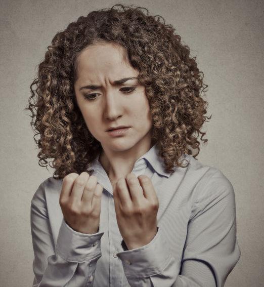 woman performing compulsive behavior by emotionally staring at nails