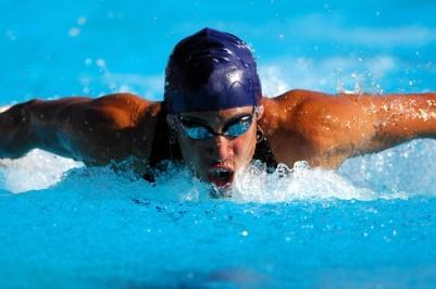 Athlete swimming while training muscles with strong inspirations