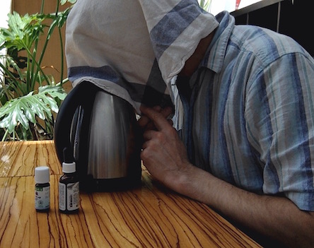Man inhaling at home hot vapor from a kettle as a remedy for chest infection