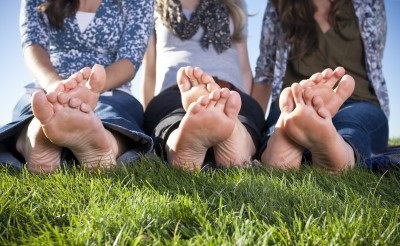 3 girls sitting on grass barefoot