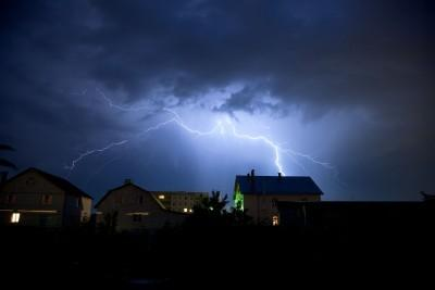 Lighting strikes the houses at night