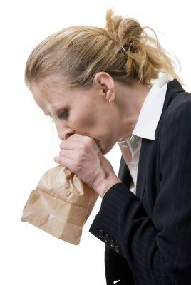 Hyperventilation Treatment - Woman breathing in paper bag for treatment of hyperventilation